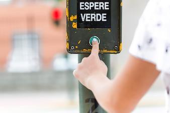 Human hand pressing green wait signal