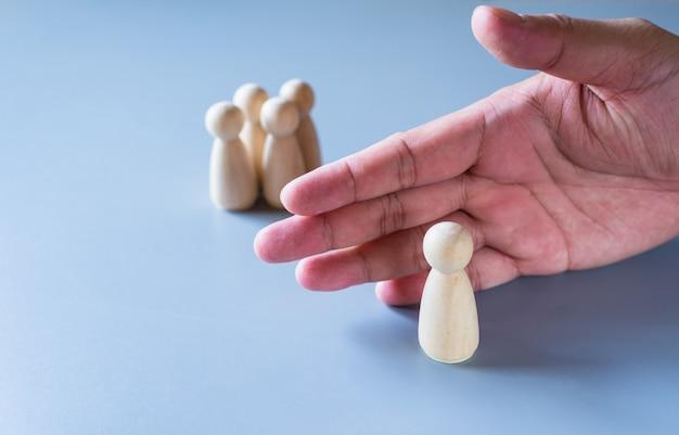 인간의 손으로 그룹의 나무 인형이 자기 격리 또는 사회적 거리 개념을 나타냅니다.