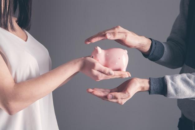 貯金箱を保護する人間の手