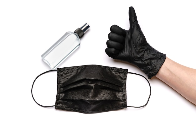 Human hand in protective glove holding face mask