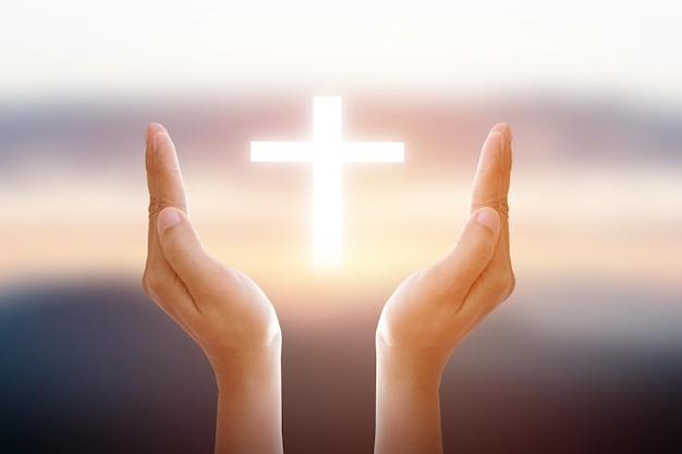 人間の手が輝く白い十字架を守る