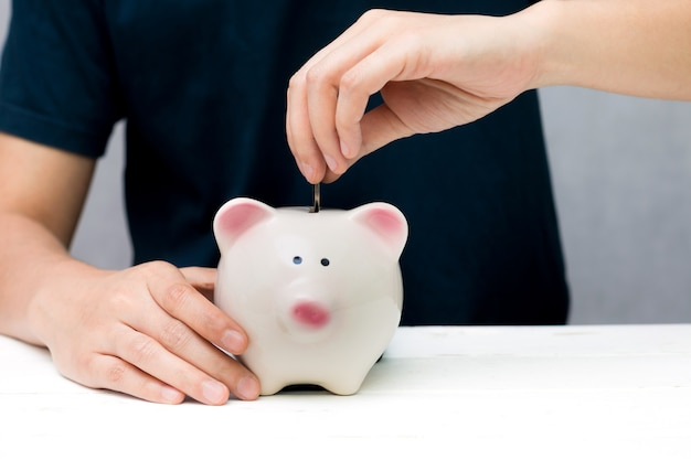 Human hand putting coin into a piggy bank. saving concept.