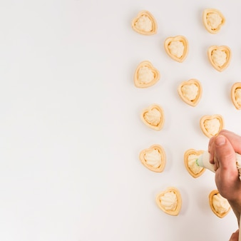 Человеческая рука кладет свежие сливки на вкусную тарталетку в форме сердца Бесплатные Фотографии