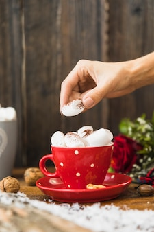Human hand putting marshmallow in cup