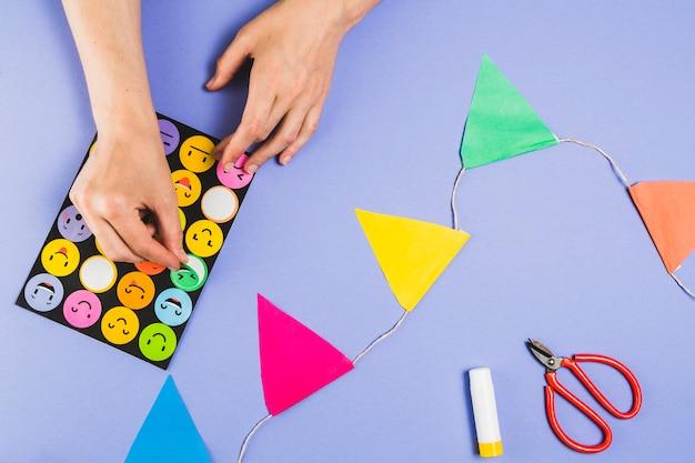 보라색 표면에 공예를 만들기 위해 설정된 스티커에서 이모티콘을 제거하는 인간의 손