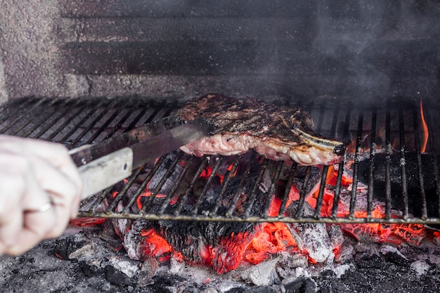 Human hand roasting meat in barbecue grill