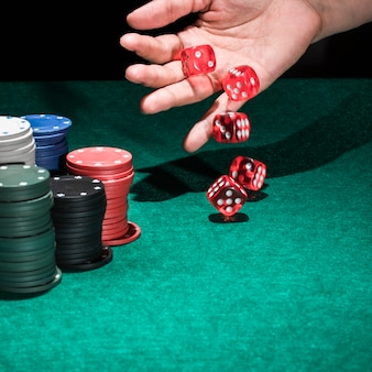 A human hand rolling several red dices in casino
