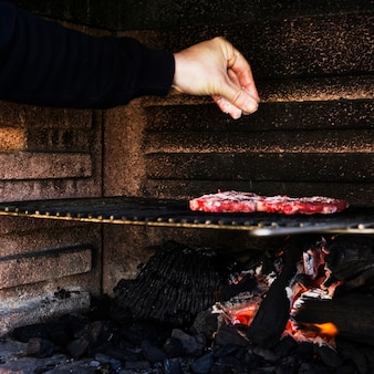 Human hand seasoning meat on barbecue grill