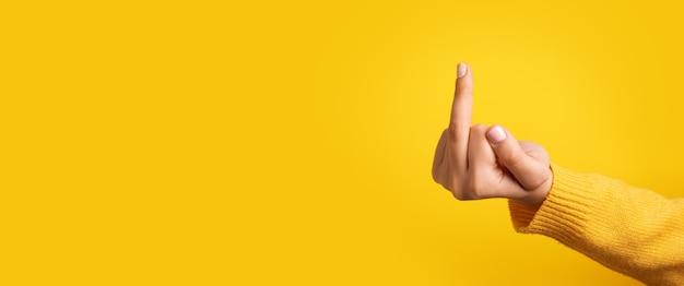 人間の手は黄色の背景、パノラマのモックアップの上に中指を表示します