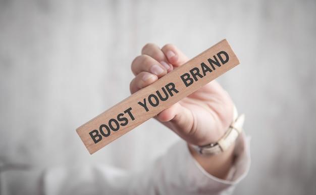 Человеческая рука показывает текст boost your brand в деревянном блоке бизнес-концепция