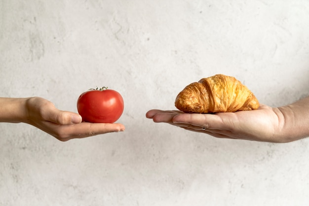 Human hand showing croissant and red tomato in front of concrete background
