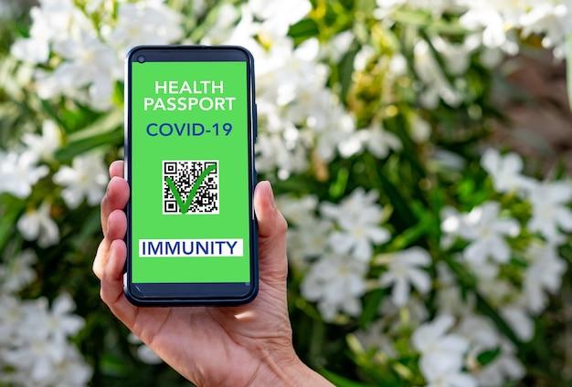 인간의 손은 코로나바이러스 covid-19 예방 접종을 받은 사람들을 위한 디지털 그린 카드 건강 여권을 보여줍니다