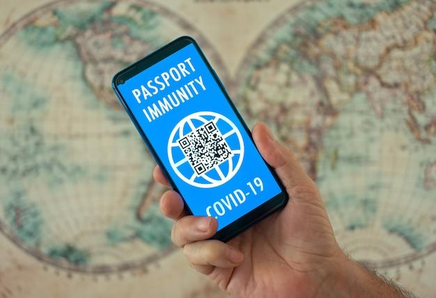 Human hand shows digital health passport app for people vaccinated against coronavirus