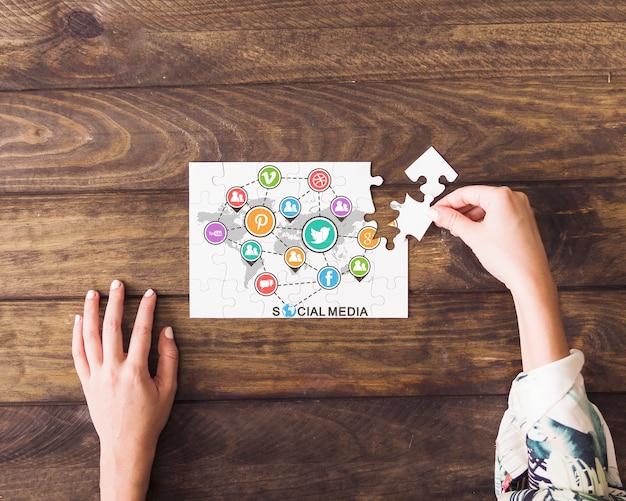 소셜 미디어 아이콘의 지 그 소 퍼즐을 해결하는 인간의 손