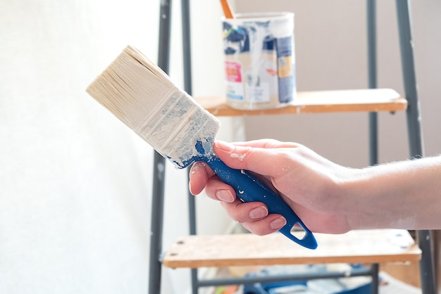 Human hand stained with paint holds brush on surface with can of paint standing on stepladder