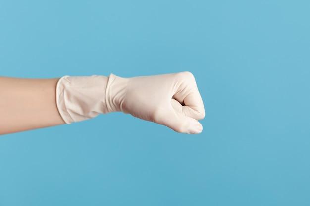 Human hand in surgical gloves showing boxing fists with hand. attack or defence against problems.