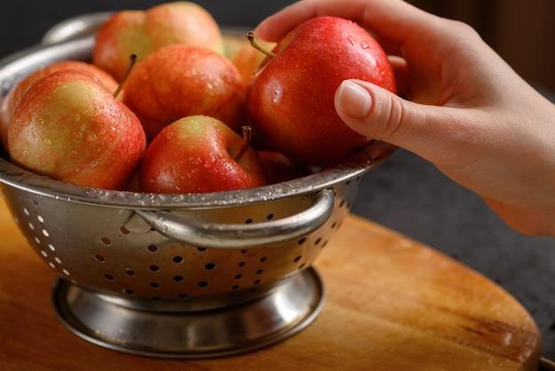 人間の手は、赤い熟したリンゴでいっぱいの金属製のボウルからリンゴを1つ取ります。健康的な食事。アップルパイの成分。家庭での料理