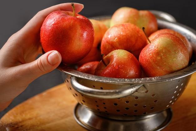 Человеческая рука берет одно яблоко из металлической миски, полной красных спелых яблок. здоровое питание. ингредиенты для яблочного пирога. готовим дома