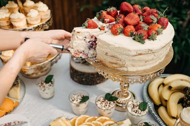 ホイップクリームとイチゴのケーキを取って人間の手