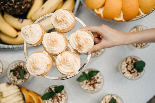 ホイップクリームとカップケーキを取る人間の手