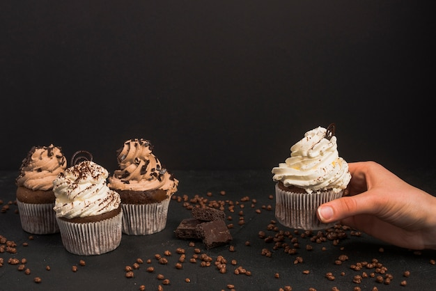 Human hand taking out muffin against black background