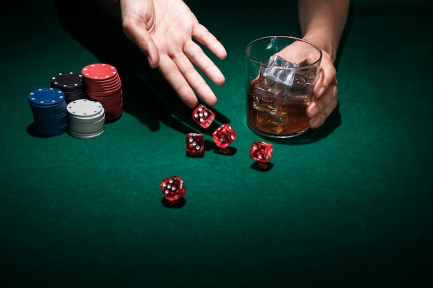 Human hand throw red dice while holding glass of whiskey