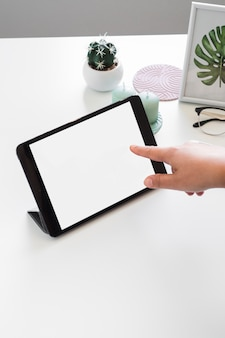 Human hand touching tablet near photo frame and eyeglasses on table