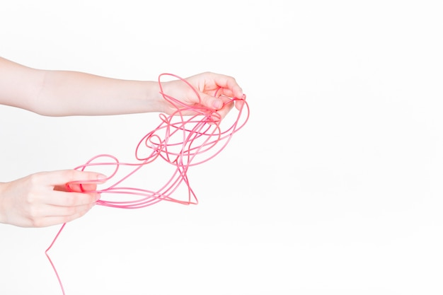 Human hand trying to untangle red wire on white background