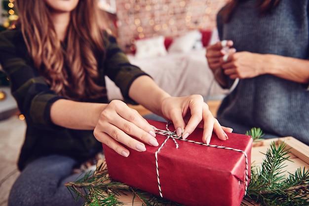 クリスマスプレゼントにひもを結ぶ人間の手