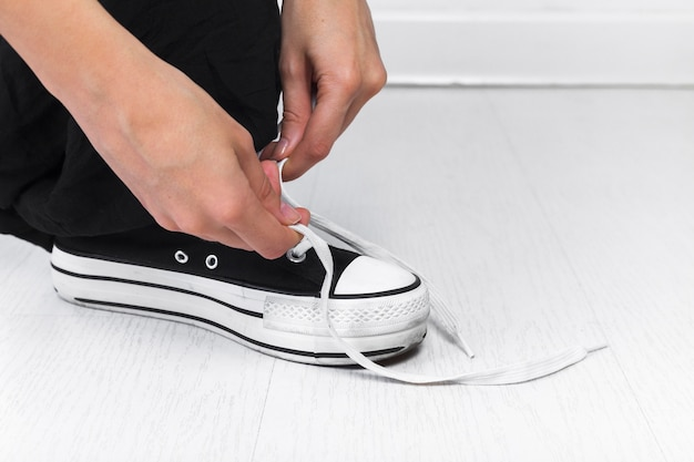 Human hand tying shoelace