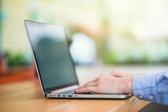 Human hand typing on laptop keypad