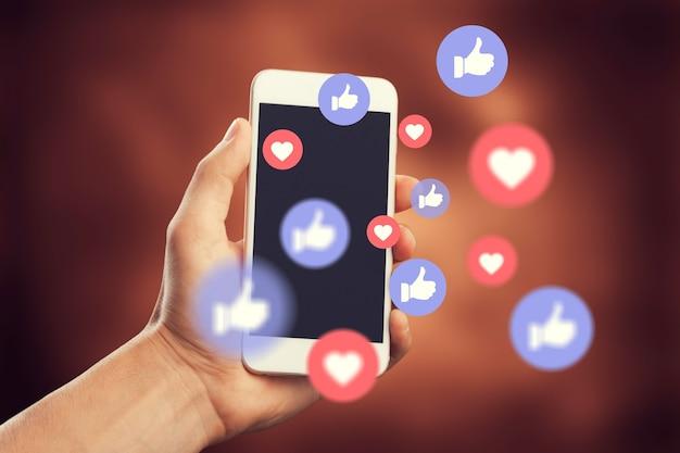 소셜 미디어 일러스트와 함께 스마트 폰을 사용하는 인간의 손