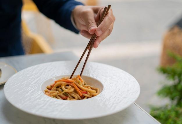 Человеческая рука, поднимающая удон палочками для еды к овощам