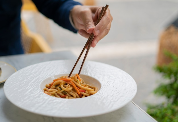 Human hand which raises the udon to the vegetables with chopsticks