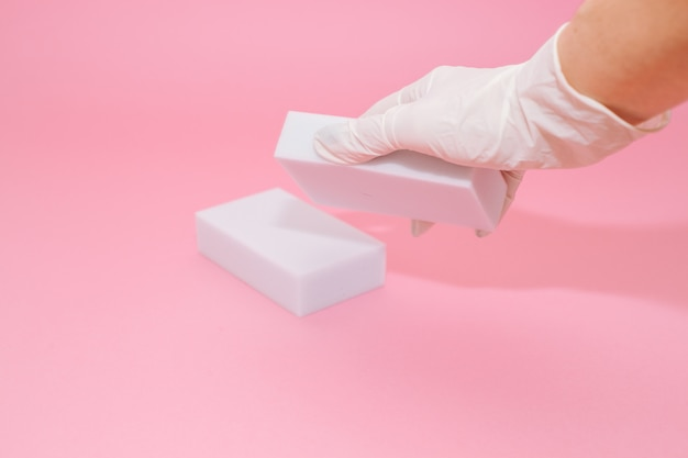 Human hand in white glove holds a white melamine household sponge for cleaning on pink background.