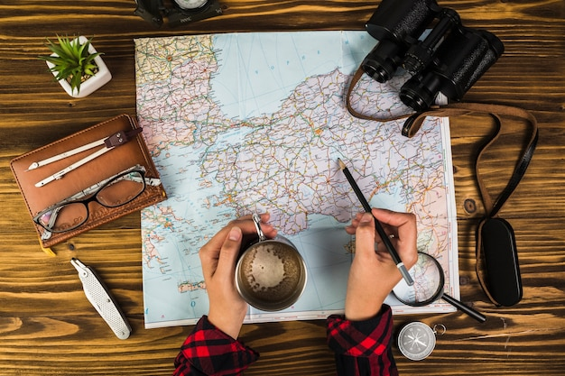Human hand with cup of coffee marking destinations on map