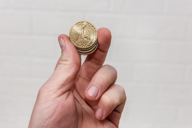 Human hand with golden dollar coins on light background