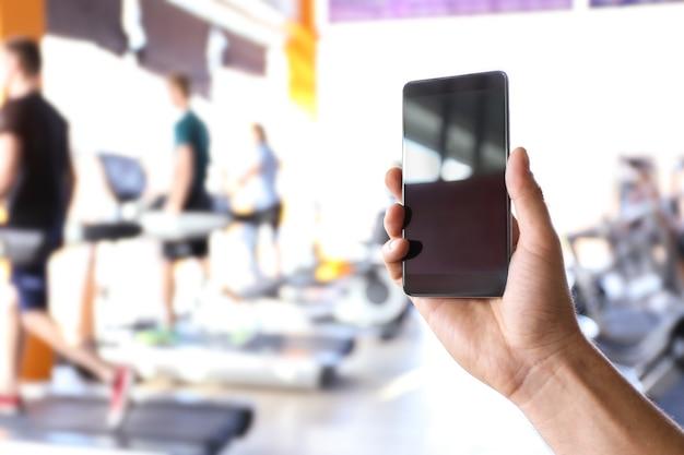 휴대 전화 및 흐리게 체육관 인간의 손