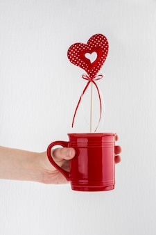 Human hand with mug with ornament heart on wand