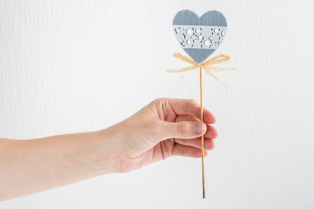 Human hand with ornament heart on wand