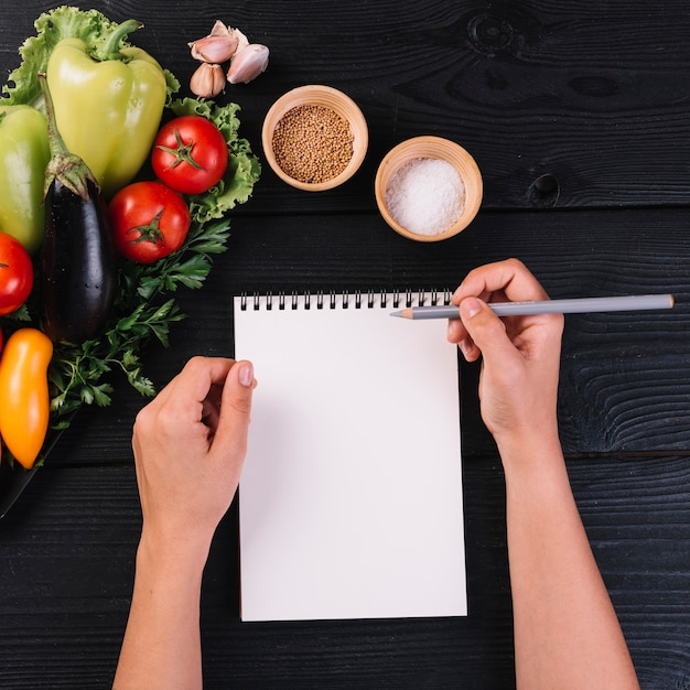 Human hand with spiral notepad and pencil near vegetables and spices on black wooden backdrop
