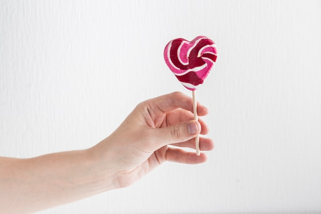 Human hand with tasty lollipop