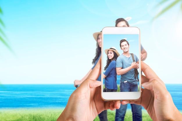 바다 배경으로 현장에 여행 아시아 부부의 사진을 찍는 휴대 전화와 인간의 손