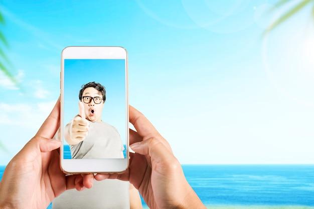 바다 배경으로 필드에 엄지 손가락을 보여주는 아시아 남자의 사진을 찍는 휴대 전화와 인간의 손