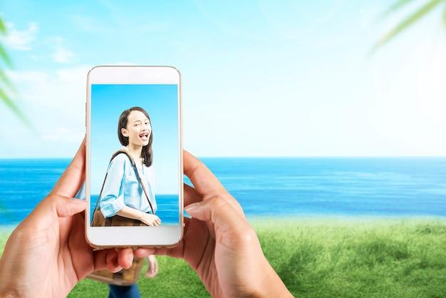 바다 배경으로 필드에 가방 여행 아시아 여자의 사진을 찍는 휴대 전화와 인간의 손