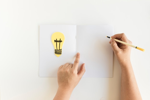 Human hand writing on card with light bulb