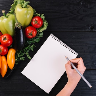 Human hand writing on spiral notepad with fresh vegetables on black wooden backdrop