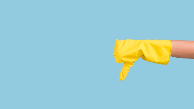 Human hand in yellow glove showing sign of dislike over blue wall