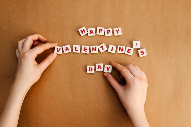 クラフト紙の背景に幸せなバレンタインデーのテキストを配置する人間の手。