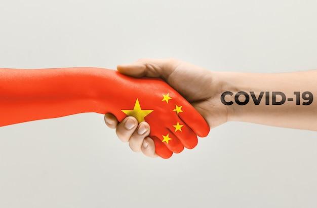 중국 국기에 색칠된 인간의 손과 바이러스 확산의 코로나바이러스 개념